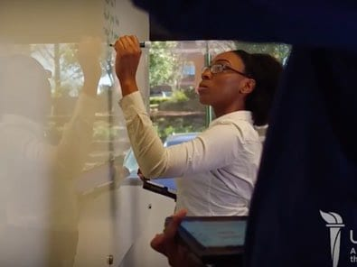 Female student writing on white board