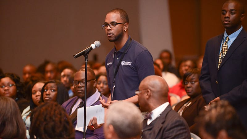 Student speaking at microphone during large gathering
