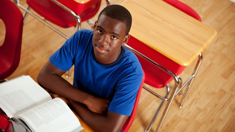 Male college student sitting at desk with text book open