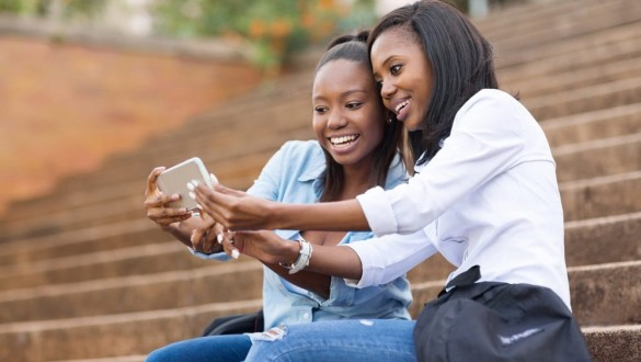Two female college students talking on a cell phone